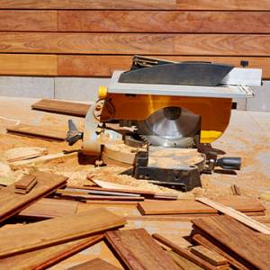 saw cutting wood planks for fence